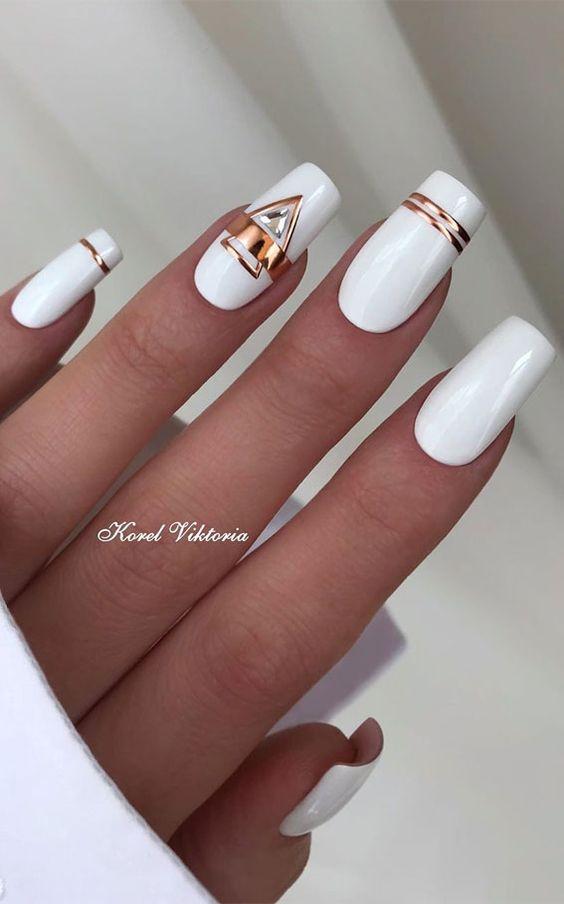 Białe paznokcie ze złotymi zdobieniami